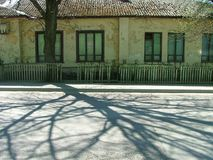 House by the street. Covered with shadows of tree trunks Royalty Free Stock Images