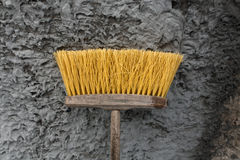 House and street cleaning yellow brush in front of wall. Royalty Free Stock Images