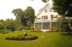 House with summer landscaping. A view of a large white house with a screened-in porch, beautiful landscaping and flower gardens Stock Images