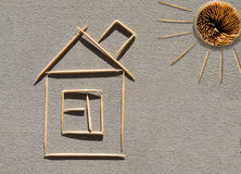 House and sun made of toothpicks on concrete stock image