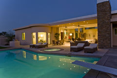 House With Sunloungers On Patio By Pool At Dusk Stock Image