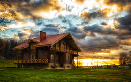 The house at sunset. The Golden light broke through the clouds Royalty Free Stock Images