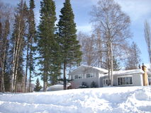 House surrounded by snow. In the central interior of British Columbia, there are high banks of plowed snow Royalty Free Stock Photo