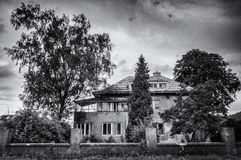 A house surrounded by tall trees and a fence. A black and white photograph of a big house surrounded by tall trees and a built up fence Stock Images