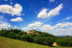 House surrounded by trees in Val d`Orcia, Tuscany, Italy. In 2004 the Val d'Orcia was added to the UNESCO list of World Heritage Sites stock photography