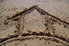 House symbol drawn in sand Royalty Free Stock Images
