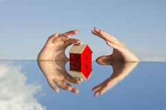 House symbol on mirror and hands Stock Image