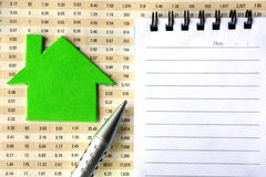 House symbol, notepad, and pen on financial report Stock Photography