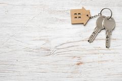 House symbol with silver keys on wood. Real estate concept Stock Photos