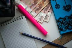 House on the table is a notebook, money, a pencil, a pink marker, a ruler, pens. stock image