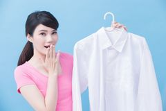Housewife take clean shirt. House take clean shirt and feel surprise on the blue background stock photo
