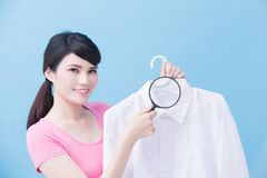 Housewife take clean shirt. House take clean shirt and magnifying on the blue background royalty free stock photo