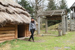 House with thatch roof in open-air museum. Smiling girl - young Papuan woman going out from door of house with thatch roof in open-air museum with traditional Royalty Free Stock Photos
