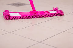 House tile cleaning with pink mop Royalty Free Stock Images