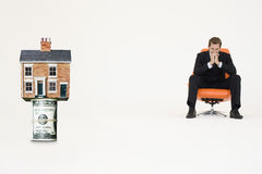 House on top of roll of bills with pensive businessman on chair representing expensive real estate Stock Images