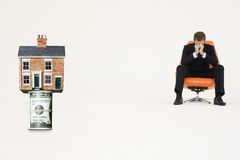 House on top of roll of bills with worried businessman on chair representing expensive real estate Stock Photo