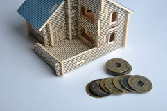 House toy and aged copper coin. A house model and aged Chinese copper coins. means real estate, investment, expensive, and money consume history Royalty Free Stock Photos