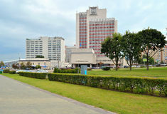 House of trade unions. View of the hotel Jubilee and the trade unions house Winners Avenue in Minsk. In the foreground pavement, shrub and lawn with green grass Stock Images