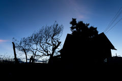House and tree silhoutte. Black silhoutte of house and tree at sunset time.Taken near Pasto, south of Colombia Stock Image