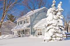 House and tree after snowstorm. Suburban house and tree covered by drifted and blowing snow after a heavy winter snowstorm Royalty Free Stock Images