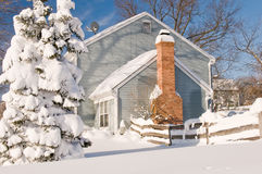House and tree in winter snow. Suburban house and tree covered by drifted and blowing snow after a heavy winter snowstorm Stock Image