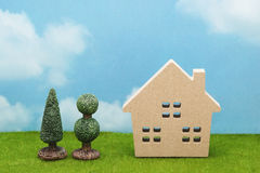 House and trees on green grass over blue sky and clouds. Royalty Free Stock Image