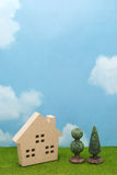 House and trees on green grass over blue sky and clouds. Mortgage concept Royalty Free Stock Photography