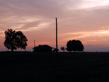 House and trees silhouette at sunset. Two trees and a house in silhouette at sunset Stock Images