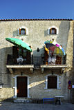 House. Typical Mediterranean stone house with colorful umbrellas at balconies at sunny summer day Stock Images