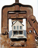 House under clamp. Clamp putting pressure on a house royalty free stock photo