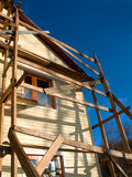 House Under Construction. With wooden scaffolding next to house Royalty Free Stock Photo