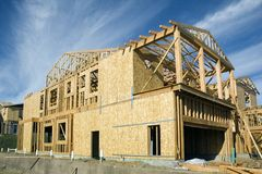House under construction. Construction jobsite with house under construction showing framing stage with some shear on the walls Stock Image
