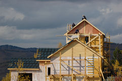 House under Construction. A new wood framed house under construction with carpenters on the roof Stock Photo