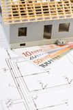 House under construction and currencies euro with electrical diagrams for project, building home cost concept. Small house under construction and currencies euro Royalty Free Stock Photos