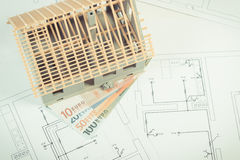 House under construction and currencies euro on electrical drawings and diagrams for project, building home cost concept. Small house under construction and Stock Images