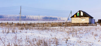 House under construction on the edge of the village.Winter landscape.  Royalty Free Stock Image