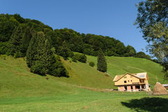 House under construction in the green hills covered with green forest and clear blue sky Stock Photography