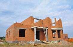 House under construction. New brick building house construction with doorway columns, windows, balcony. Royalty Free Stock Images