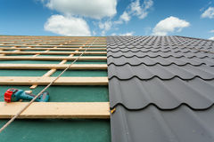 House under construction.Roof with metal tile,screwdriver and roofing iron. royalty free stock images