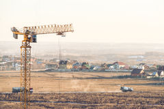 House under construction with a tower crane and two trucks on background Royalty Free Stock Photography