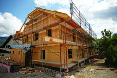 House Under Construction. Wooden house under construction with scaffold all arround it Stock Photo