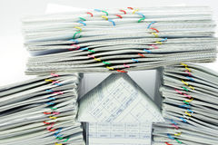 House under document with heart-shaped clips. And dual pile overload document with colorful paper clips on a white background Stock Photos