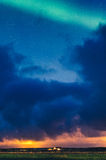 House under heavy clouds and northern lights Royalty Free Stock Image