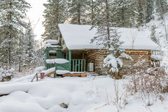 House under snow in winter wood chalet among spruce trees in the Royalty Free Stock Image