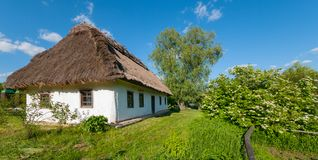 House under a thatched roof with white walls in the countryside against a blue sky. royalty free stock images