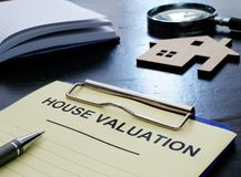 House valuation concept. Documents in clipboard and small home. House valuation concept. Documents in clipboard and small wooden home stock images