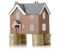 House value. House propped up with money isolated on a white background Stock Photos
