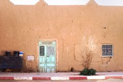 House in the village with cat and pistachio steel doors during sunny day on the outskirts of Sahara Desert. Morocco, Africa royalty free stock images
