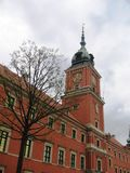 The house with a wall clock on a tower in Warsaw. Stock Photos