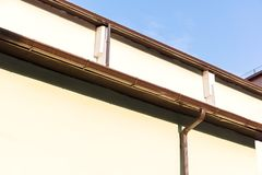 House wall with gutter and drainpipe on blue sky background Royalty Free Stock Photo